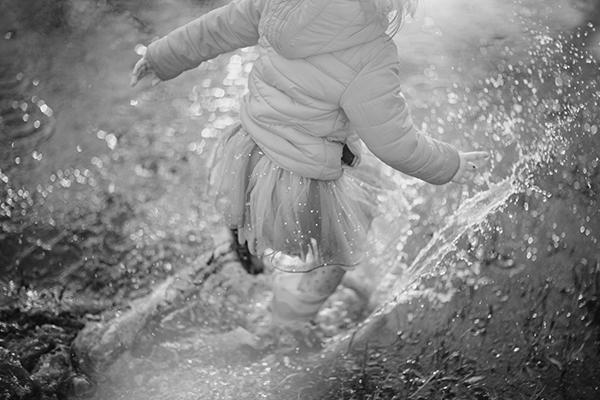Child spashing through puddle