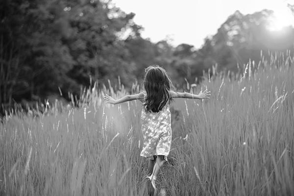 Child walking through field